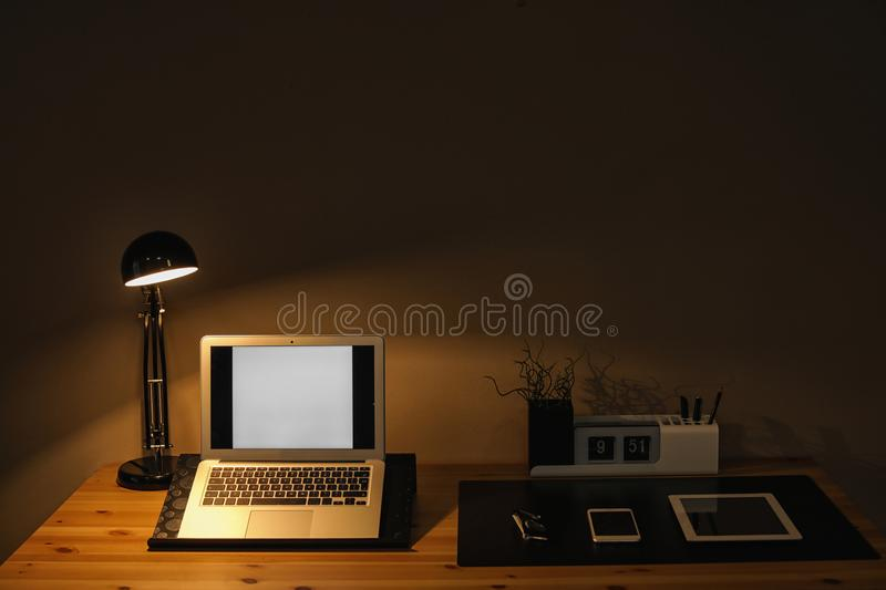 Dark room interior with laptop and devices on table. Space for text stock images