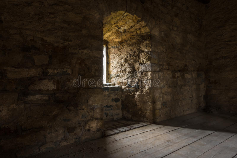 Dark room with stone walls window and wooden staircase.  royalty free stock photo