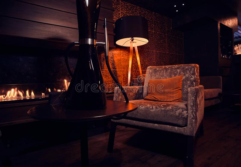 Dark room with working fire place, velvet armchair, lamp and black hookah stock photo