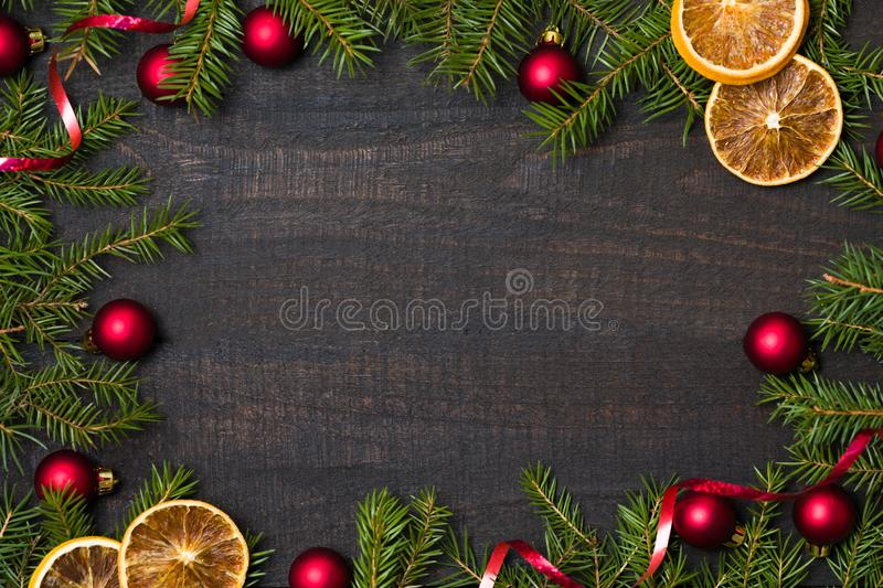 Dark rustic wood table flatlay - Christmas background with decoration and fir branch frame. Top view with free space for copy stock photography