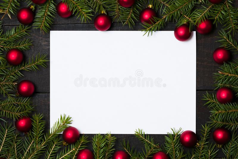 Dark rustic wood table flatlay - empty card on Christmas background with red ball ornament decoration and fir branch frame. Top royalty free stock photography