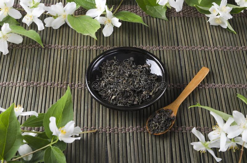 Dark saucer and green tea leaves on it, wooden spoon, fresh jasmine flowers on green serving mat stock images