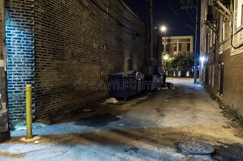 Dark and scary downtown urban city street corner alley at night. Dark and scary downtown urban city street corner alley with an eerie vintage industrial stock images