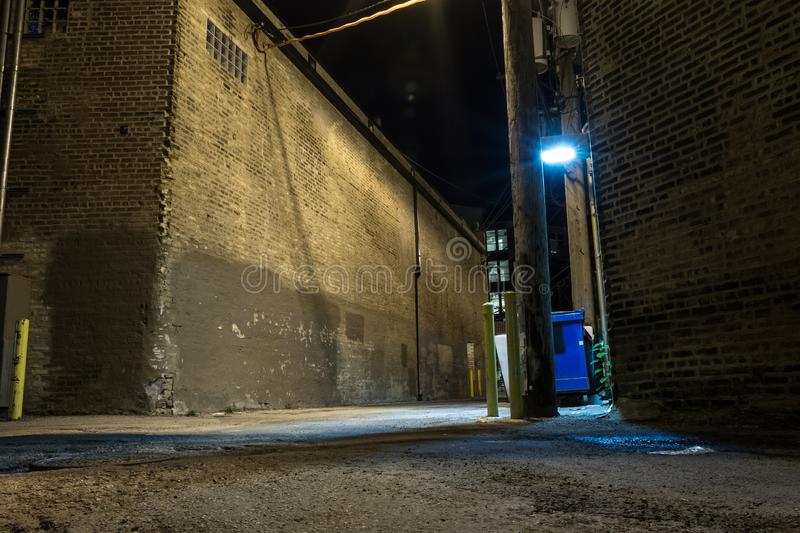 Dark and scary downtown urban city street corner alley at night. Dark and scary downtown urban city street corner alley with an eerie vintage industrial stock photography
