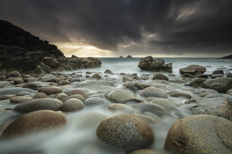 Dark scenery of the ocean shore full of rocks in Nr. Lands End, Cornwall, UK. A dark scenery of the ocean shore full of rocks in Nr. Lands End, Cornwall, UK royalty free stock image
