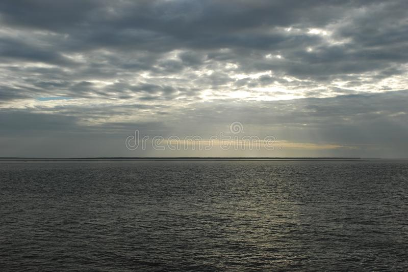 Dark sea with clouds. Dark looking sea, with sunlight streaming through the clouds stock photography