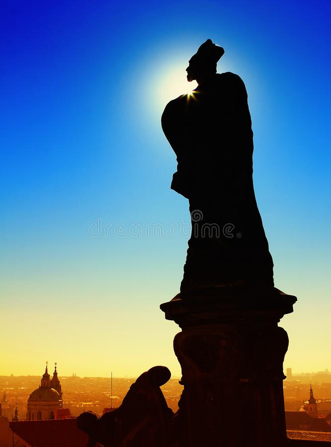 Dark shadow of statue. On the bridge with old town and blue sky background stock photography