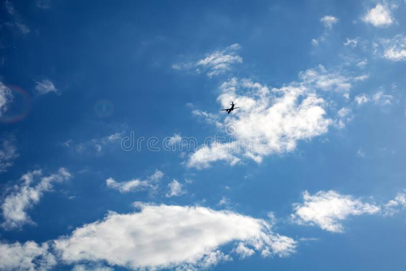 Dark silhouette of airplane flying over the blue skies.  royalty free stock photos