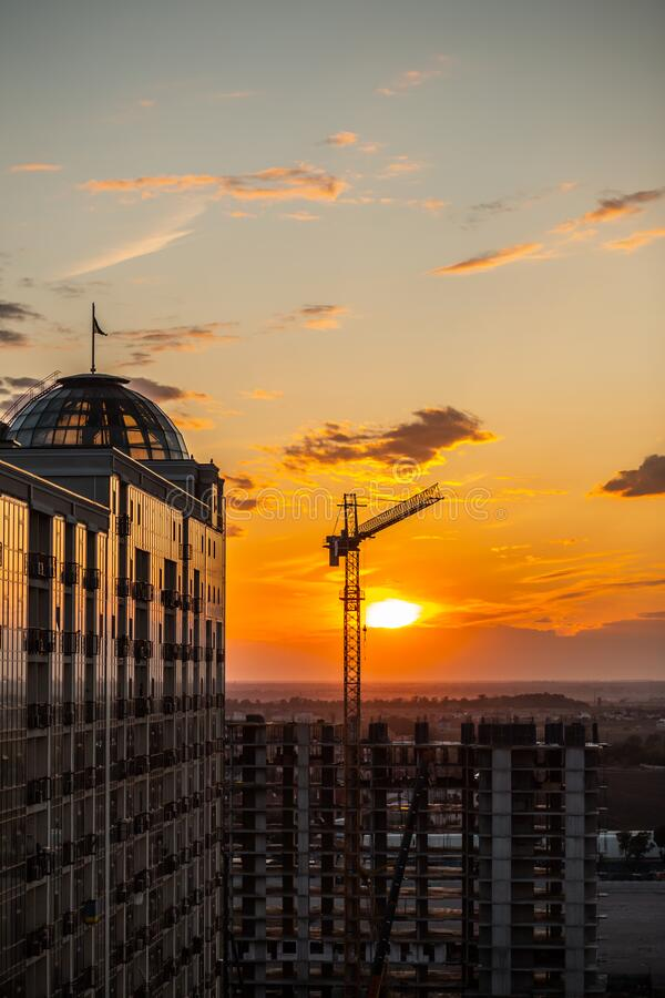 Dark Silhouette of construction crane and building from glass on sunset sky background. Used for lifting equipment in the royalty free stock photography