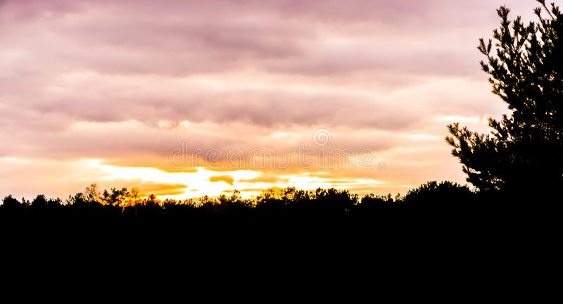 Dark silhouette of a forest landscape scenery at sunset, sundown giving a beautiful effect in the sky and clouds stock photo