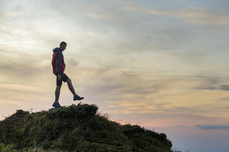 Dark silhouette of a hiker balancing on a summit stone in evening mountains stock images