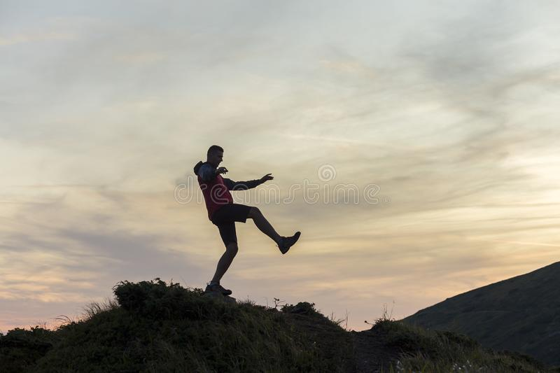 Dark silhouette of a hiker balancing on a summit stone in evening mountains royalty free stock photography