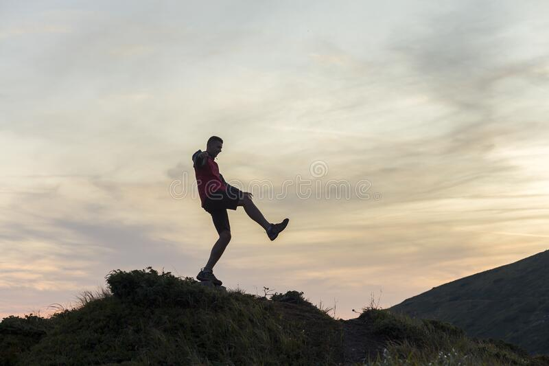 Dark silhouette of a hiker balancing on a summit stone in evening mountains royalty free stock images
