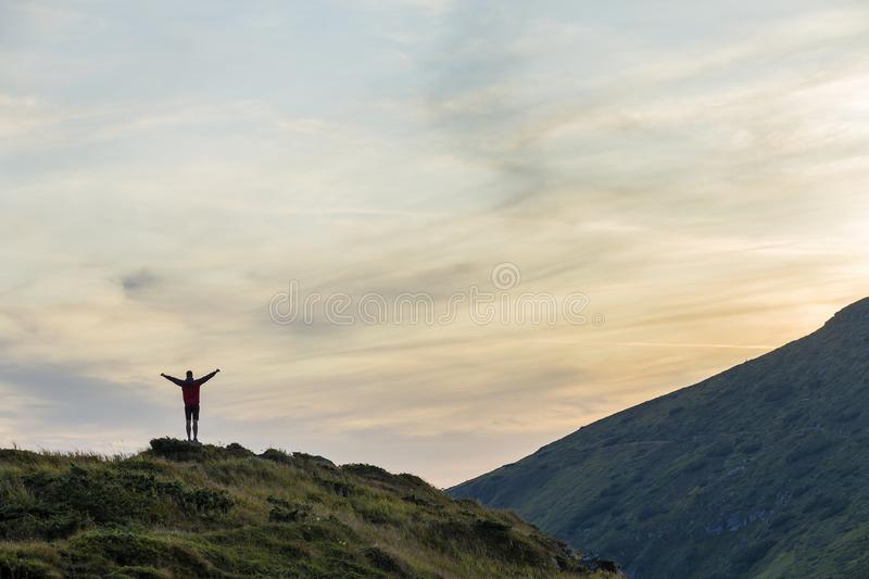 Dark silhouette of a hiker climbing a mountain at sunset raising his hands standing on summit like a winner stock photos