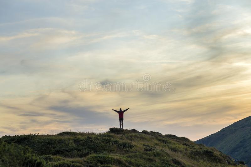 Dark silhouette of a hiker climbing a mountain at sunset raising his hands standing on summit like a winner royalty free stock photography