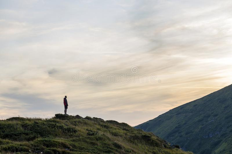 Dark silhouette of a hiker on a mountain at sunset standing on summit like a winner royalty free stock images