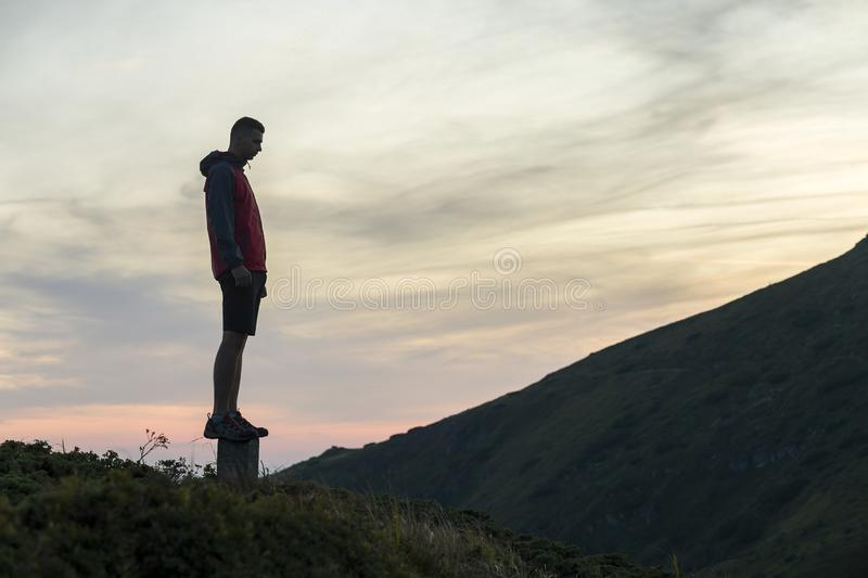 Dark silhouette of a hiker on a mountain at sunset standing on summit like a winner royalty free stock image