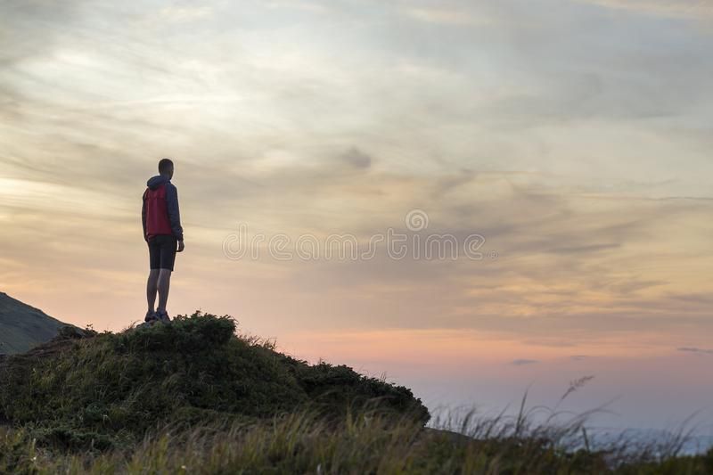 Dark silhouette of a hiker on a mountain at sunset standing on summit like a winner royalty free stock photography