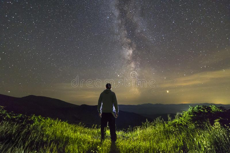 Dark silhouette of a man standing in mountains at night enjoying milky way view royalty free stock photo