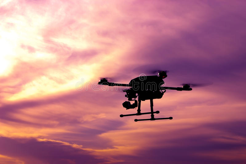 Dark silhouette of self-assembled drone hovering in a colorful s. Unset. Toned image. Soft focus royalty free stock photography