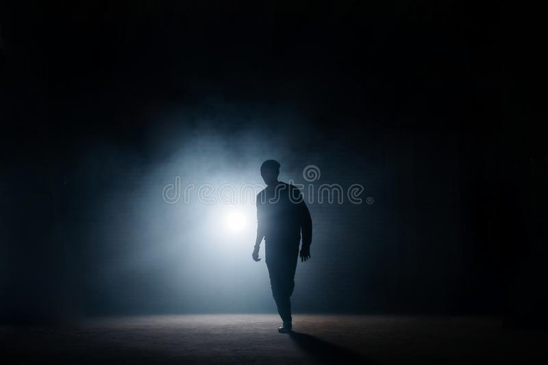 Dark silhouette of slim man walking on the street at night stock photos