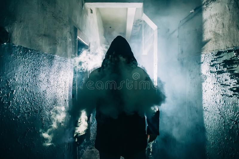 Dark silhouette of strange danger man in hood in back light with smoke or fog in scary grunge corridor or tunnel stock images