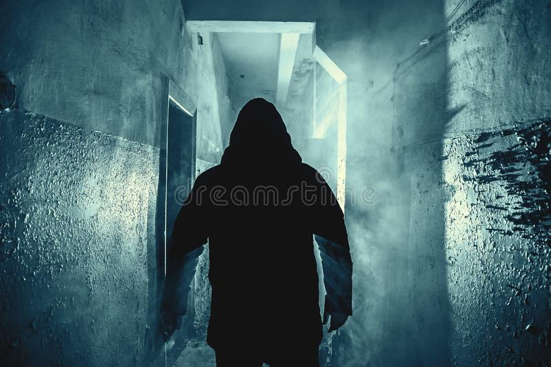 Dark silhouette of strange danger man in hood in back light with smoke or fog in scary grunge corridor or tunnel royalty free stock photos