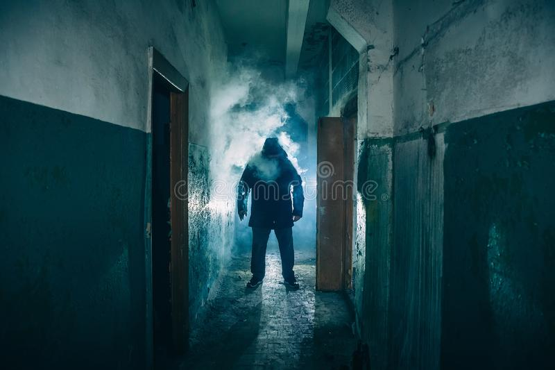 Dark silhouette of strange danger man in hood in back light with smoke or fog in scary grunge corridor or tunnel stock image