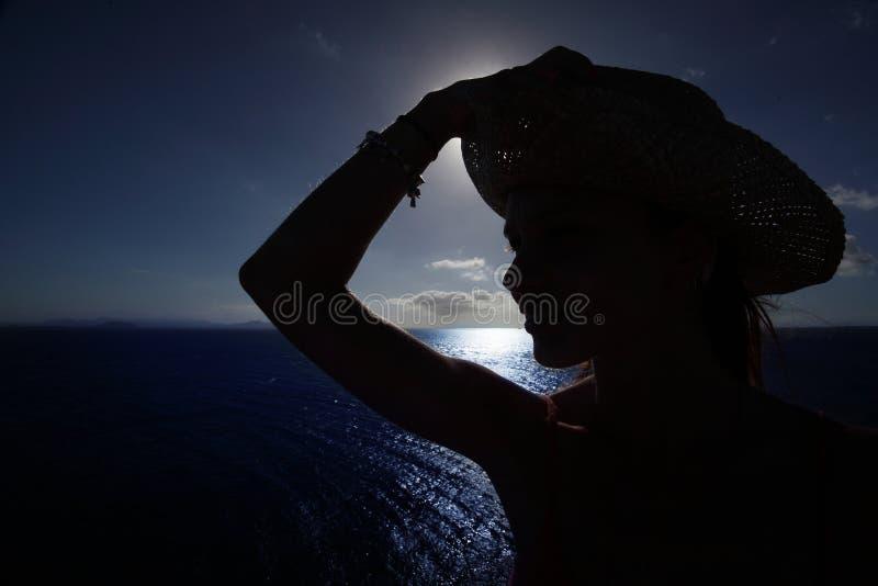 Dark silhouette. woman walking in hat, closeup portrait, coast on Lanzarote, Canary Islands, Spain, summer stock image