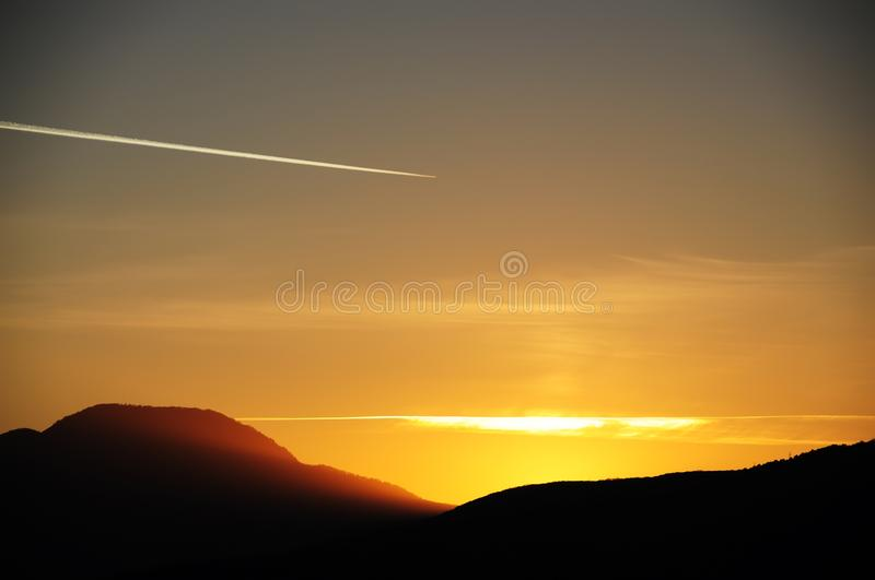 Dark silhouettes of mountains at sunset, trail from an airplane in the sky. royalty free stock image