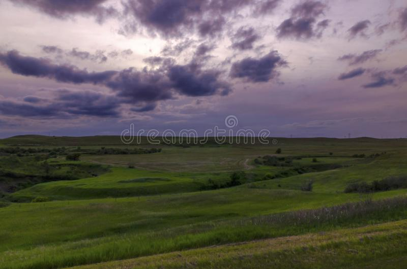 Dark skies over meadows. Dramatic clouds float across the sky at the blue hour over green meadows royalty free stock photo