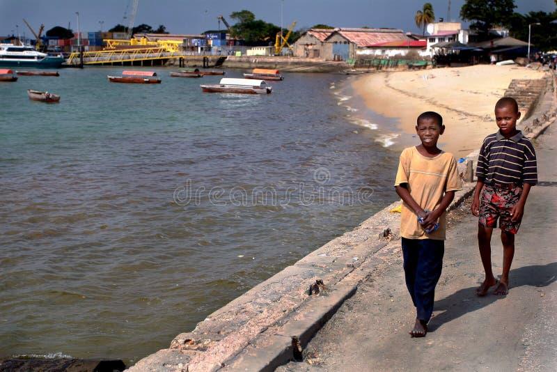 Dark-skinned Africans teenagers, 12 years old, walking along sea stock photo