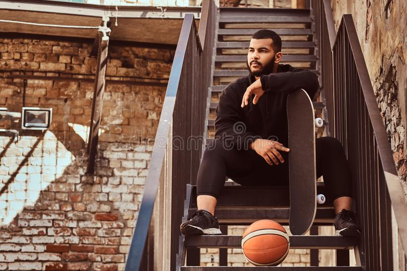 Dark skinned bearded hipster guy dressed in a black hoodie and sports shorts holds a skateboard while sitting on stairs royalty free stock images