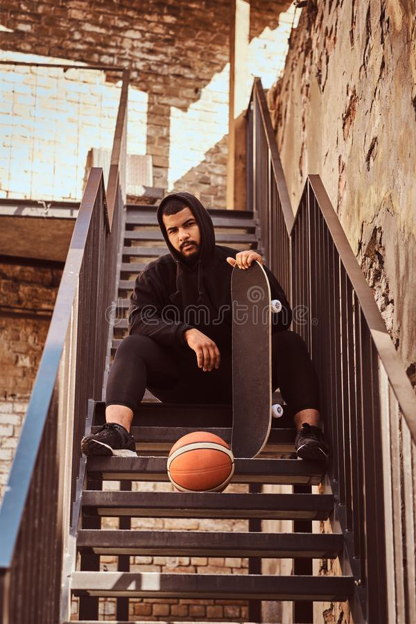 Dark skinned bearded hipster guy dressed in a black hoodie and sports shorts holds a skateboard while sitting on stairs stock image