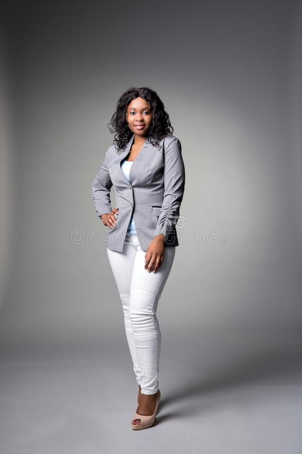 Dark-skinned beautiful woman in a gray jacket and white jeans with dark curly hair posing on a gray background stock photo