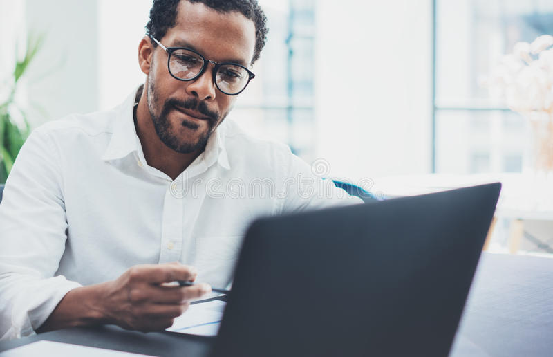 Dark skinned coworker wearing glasses and using laptop in modern office.African american man in white shirt working on royalty free stock photography