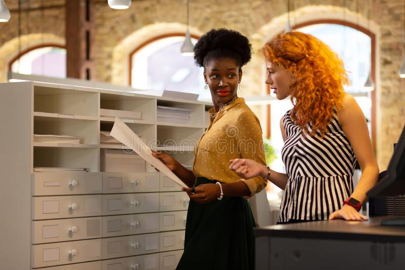 Dark-skinned employee asking something while talking to boss. Employee asking. Dark-skinned employee asking something while talking to experienced red-haired royalty free stock images