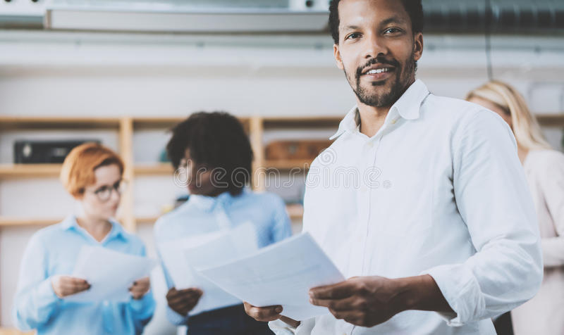 Dark skinned entrepreneur holding papers in hands and smiling at the camera.Teamwork concept in modern office royalty free stock photos