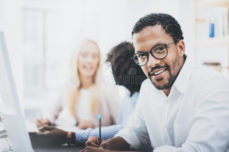 Dark skinned entrepreneur wearing glasses, working in modern office.African american man in white shirt looking and smiling at the stock photography