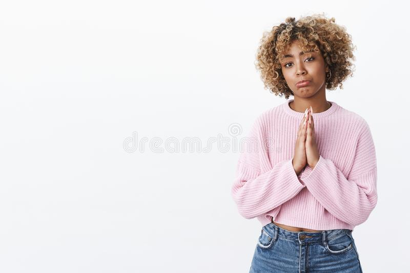 Dark-skinned girl begging pursing lips sulking and holding hands in pray, supplicating asking apology or forgiveness. With hopeful cute expression standing over stock image