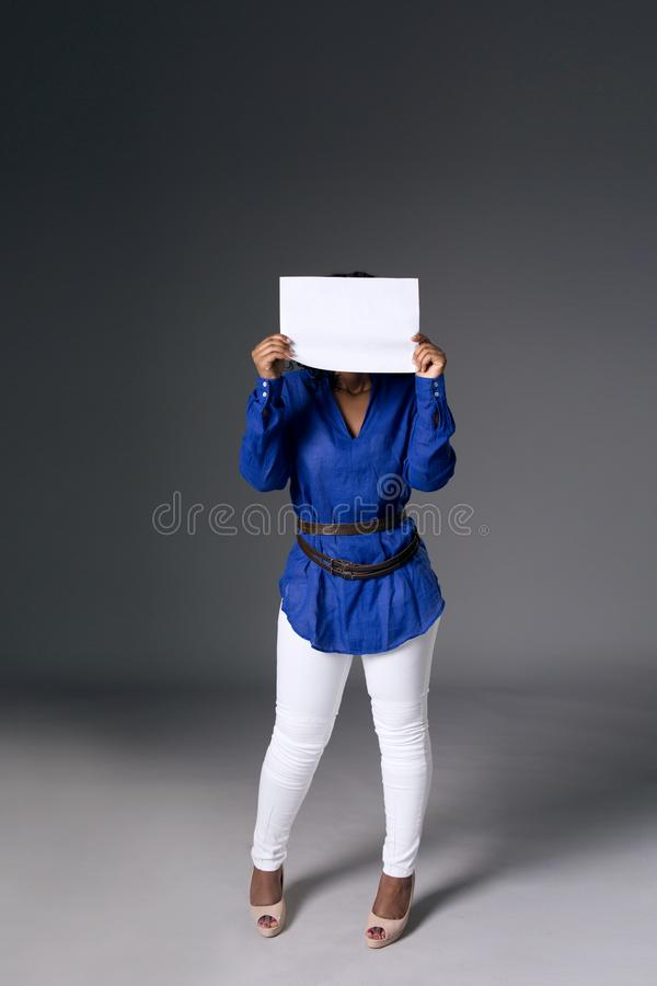 A dark-skinned girl in a blue shirt covered her face with a white sheet with space for text royalty free stock images