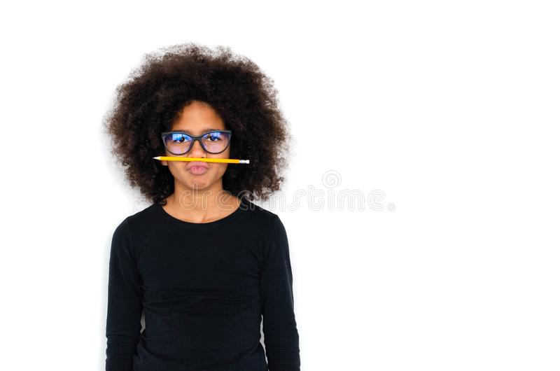 Dark-skinned girl funny holding a simple pencil stock photo