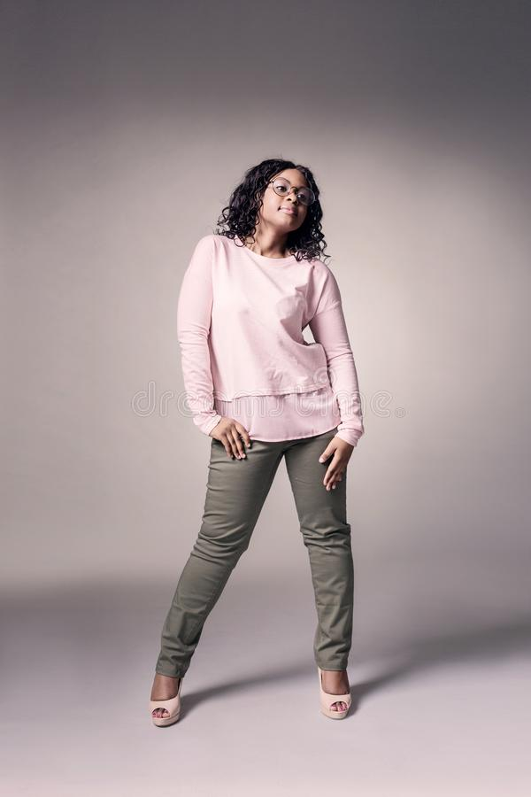 A dark-skinned girl in a rose jacket and green jeans posing over royalty free stock images
