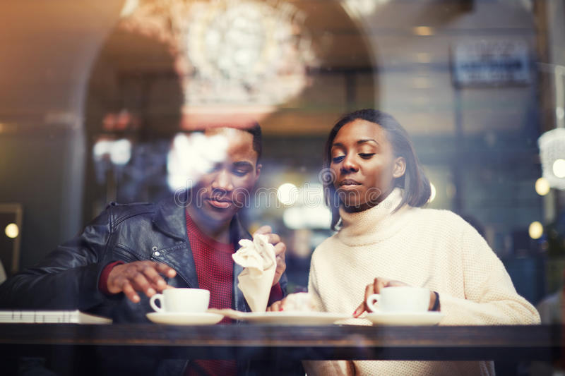 Dark skinned man and woman sitting together in coffee shop interior while rest after walking outdoors and drink cafe,. Two friends relaxing after strolling in royalty free stock photography