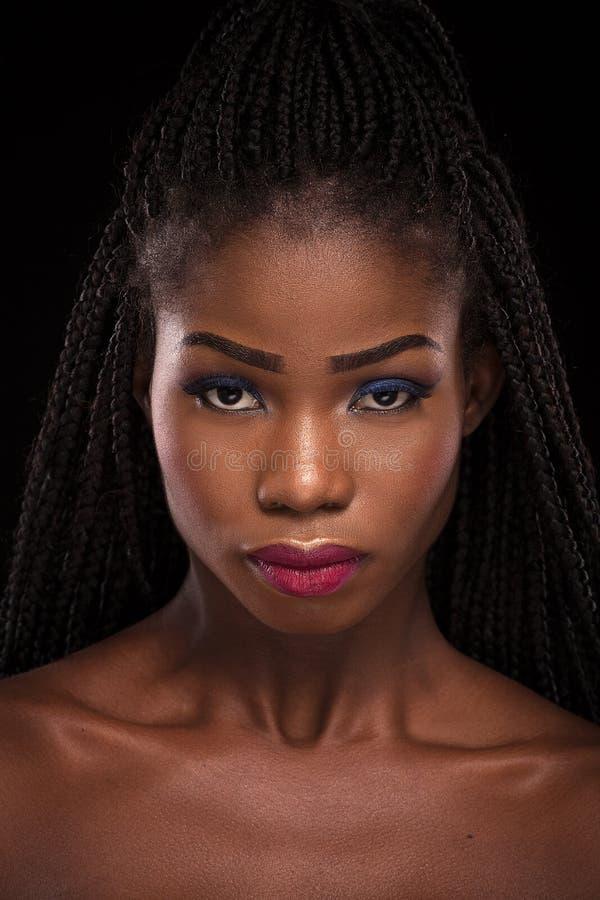 Dark skinned model posing on black background. Beautiful wowan with blue eyeshadow and pink lips posing in studio. Close up portrait of dark skinned female royalty free stock photography