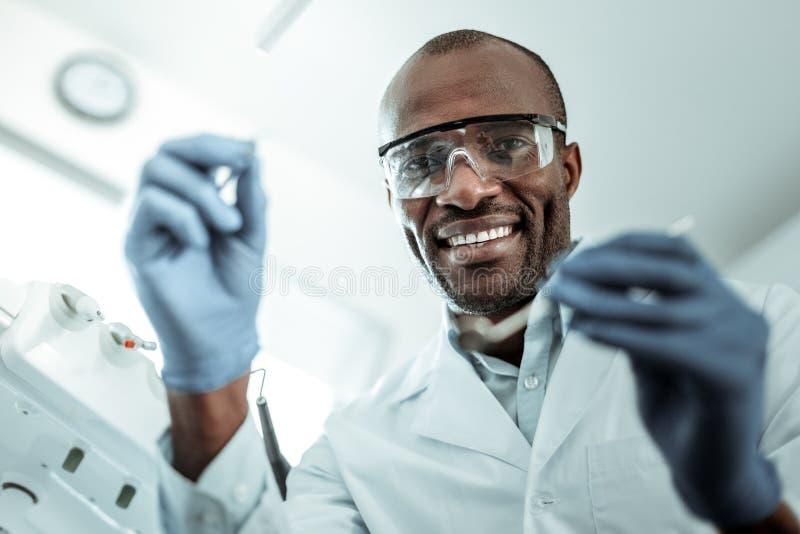 Dark-skinned stomatologist with white teeth having workday. Dentist equipment. Dark-skinned stomatologist with white teeth having ordinary workday wearing royalty free stock photography