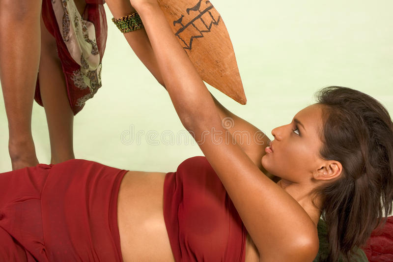 Dark skinned woman is attacked with use of spear stock photos