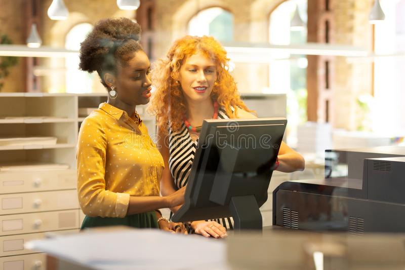 Dark-skinned young cashier asking questions to boss. Cashier asking questions. Dark-skinned cashier asking questions to boss while having probation period stock photo