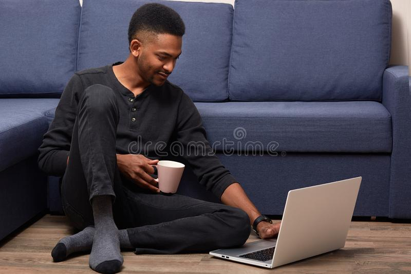 Dark skinned young male working with his laptop at home, holds cup with hot beverage, sitting near couch on floor, handsome man royalty free stock photos
