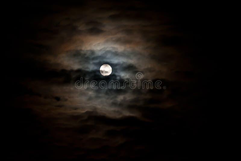 Dark sky. A bright full moon in a dark cloudy sky stock photo